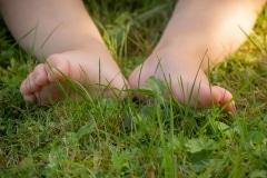Jente geniet van de grassprieten tussen haar teentjes